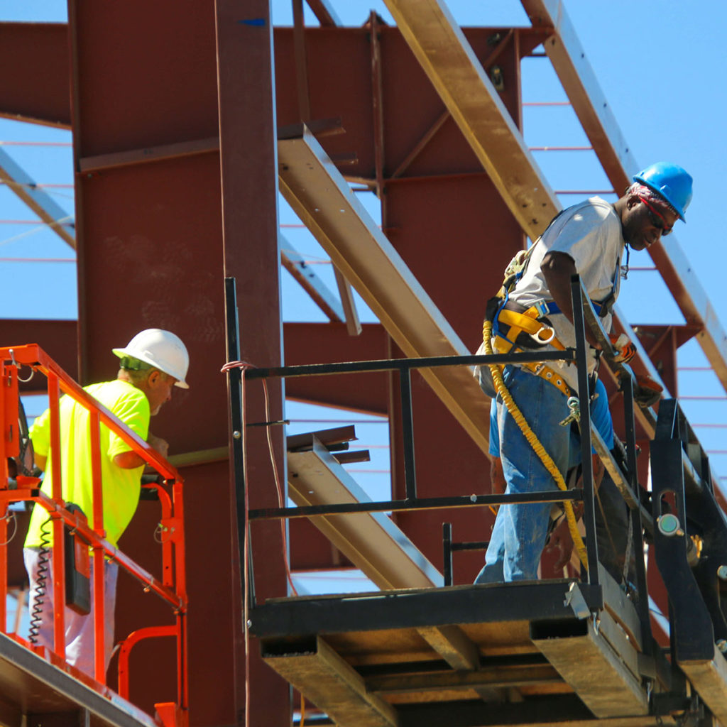 Construction workers on trusses and scissor lifts